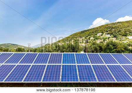 Row of blue solar collectors near greek town on mountain