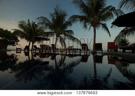 Sunset, beach chairs, palm trees, infinity swimming pool silhouette. Bali, Amed