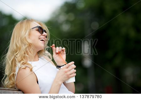 Portrait of young blonde in profile. Woman holding drink and laughing