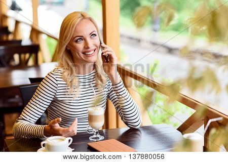Pretty blond girl is using phone for communication. She is talking and laughing. Lady is sitting at table in cafe