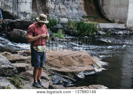 Man changing lure while fishing near the dam, standing on the rock