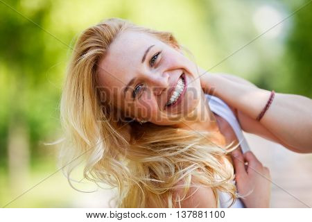 Laughing caucasian woman threw back her head and touching her neck