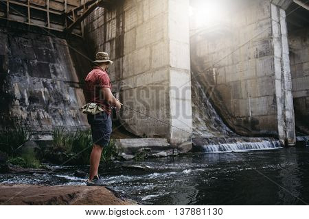 Man fishing, casting with ultralight rod near the dam standing on the rock, flare is visible in the frame