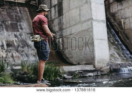 Man fishing, casting with ultralight rod near the dam standing on the rock