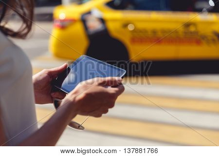 Woman holding sunglasses and touch pad nearly crosswalk. Tablet with blank copy space
