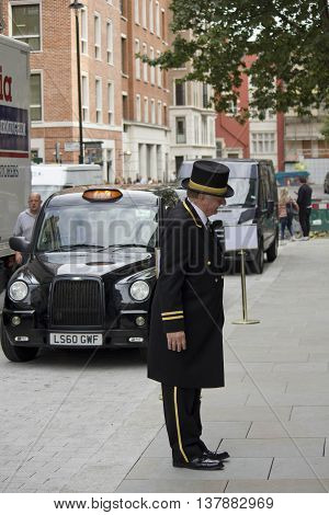 LONDON, UNITED KINGDOM - SEPTEMBER 11 2015: Concierge outside an hotel in London with a black taxi behind him