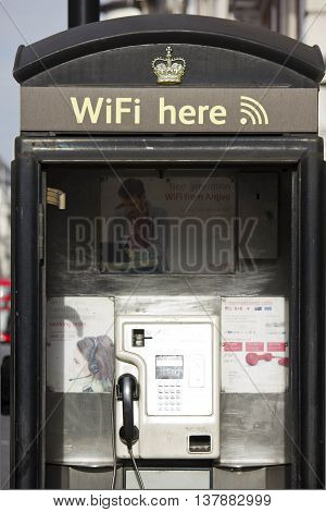 LONDON, UNITED KINGDOM - SEPTEMBER 11 2015: Modern telephone box in London with the wifi sign and crown symbol
