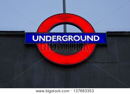 LONDON, UNITED KINGDOM - SEPTEMBER 11 2015: Close up of a traditional station sign for the London public Underground facing the sky at night time