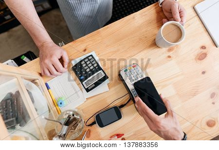 Transaction. Cropped image, top view of man paying with NFC technology on mobile phone being in coffeehouse