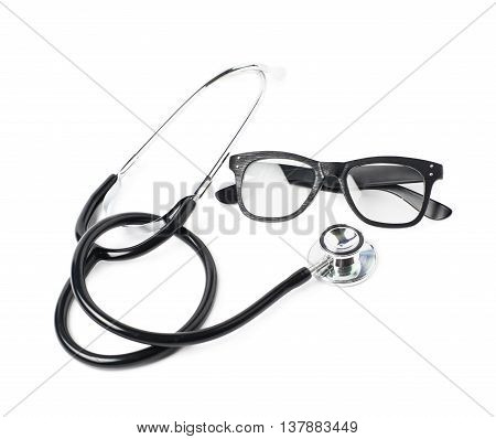 Pair of wooden textured optical reading glasses next to a medical stethoscope, composition isolated over the white background