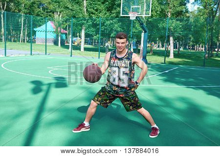 Man with basketball ball standing on green playground against the basket