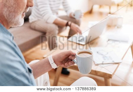 Our morning. Cropped image of man holding a cup of coffee with another man sitting, drinking coffee and using laptop in a background