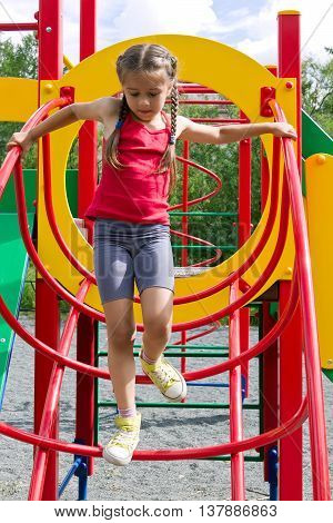 Little caucasian girl dressed in a red jersey playing on playground, coming down the stairs