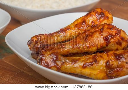 Marinated Indonesian chicken drumsticks with rice on a white plate