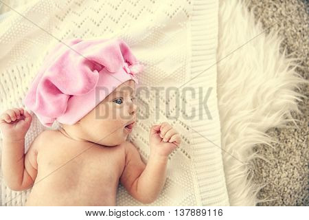Newborn baby girl, 7 days old, lying on soft blanket