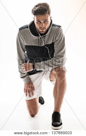 Inspired young athlete is looking at camera with desire. He is kneeling while wearing headphones. Isolated