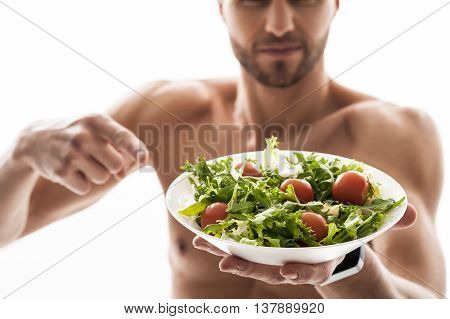 Strong male athlete prefers healthy food. He is standing and pointing finger at salad with proud. Focus on plate. Isolated
