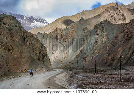 Single female cyclist on the bicycle on the remote road in Western Tibet