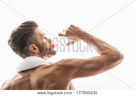 Strong young man is drinking water after training. He is standing and looking forward pensively. Man is carrying white towel on neck. Isolated