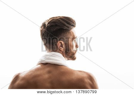 Confident young man is showing his trained naked back. He is standing with towel over neck. Isolated and copy space in right side