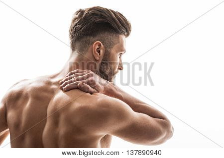 Young athlete is massaging his neck with pain. He is standing with bare back and looking forward with frustration. Isolated and copy space in right side