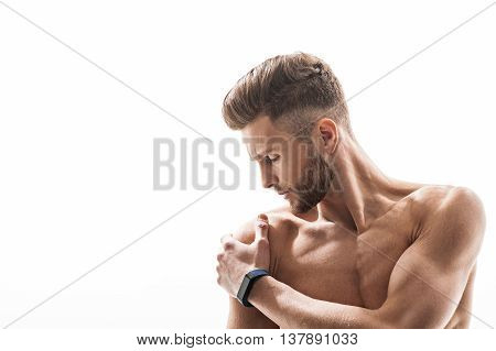 Despaired young sportsman suffers from pain in his shoulder. He is touching painful area with frustration. Isolated and copy space in left side