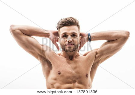 Strong young sportsman is training his body. He is raising arms behind head and smiling. Isolated