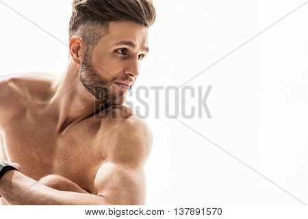 Handsome young sporty man is resting after training. He is sitting and looking aside with confidence. Isolated and copy space in right side