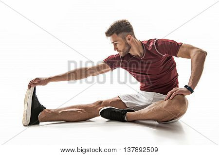Fit young man is doing exercise with concentration. He is stretching hand to foot while sitting on floor. Isolated