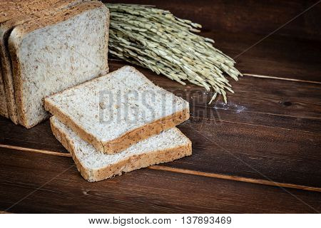 Fresh whole wheat bread on wooden background
