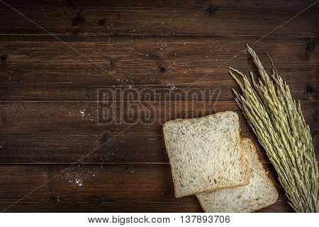 Top view of whole wheat bread on wooden background with copyspace
