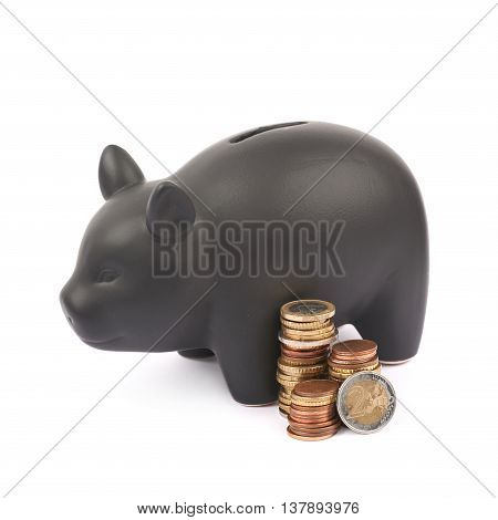 Black ceramic piggy bank coin container next to a pile of euro coins, composition isolated over the white background