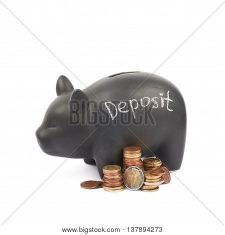 Word Deposit written with chalk on a black ceramic piggy bank coin container next to a pile of euro coins, composition isolated over the white background