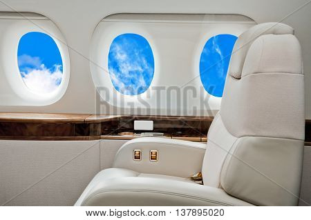 Aircraft business class interior with blue sky outside the portholes