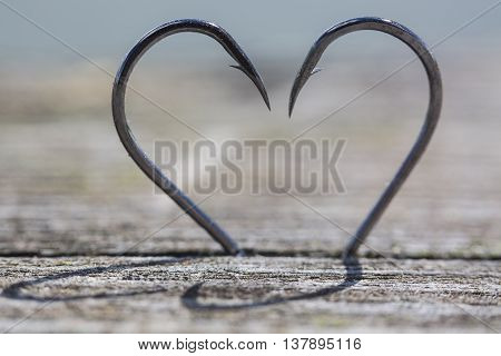 Heart Made of Two Fish Hooks on wood