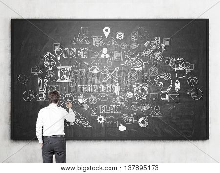 Businessman drawing chaotic business sketch on chalk board hanging on concrete wall. Back view Success concept