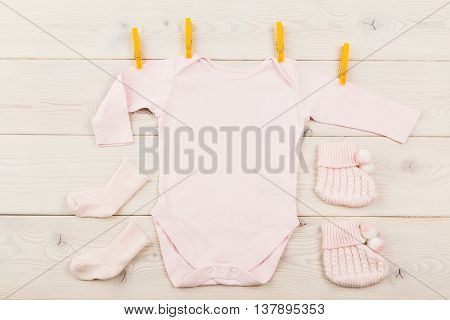 Top view of pink baby girl bodysuit with pegs and socks on light wooden table. Mock up