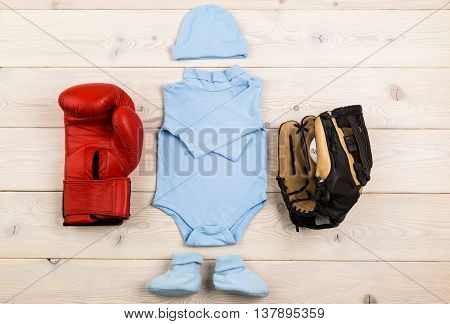 Future occupation concept. Top view of blue baby boy outfit surrounded with boxing glove and baseball equipment on light wooden table