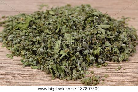 Heap of dried marjoram on wooden background seasoning for cooking concept for healthy nutrition