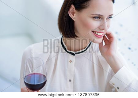 Dreamful young woman relaxing and smiling. She is holding a wineglass. Lady is sitting and looking at window happily