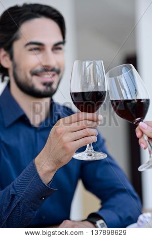 Lets drink for us. Happy young man is clinking glasses with woman and smiling. Focus on wineglasses