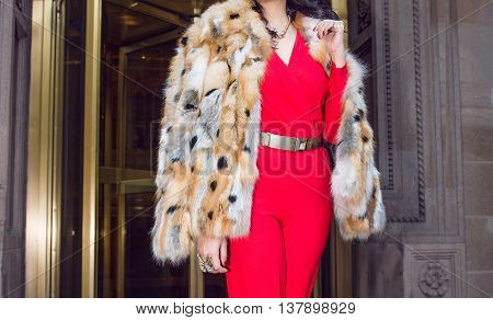 Fashionable woman wearing luxury outfit with fur coat golden belt and red custume