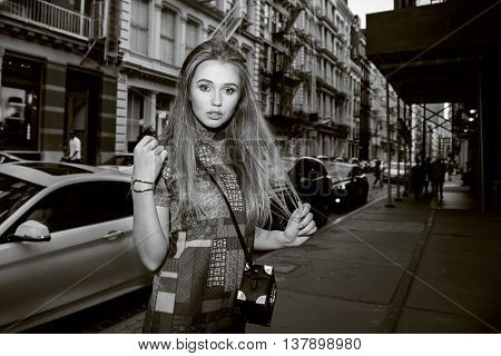 Black and white fashion photo of beatiful elegant model girl walking on the street