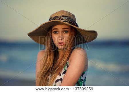 Confused girl thinking on the ocean beach. Beautiful young girl wearing hat and having fun on the beach.