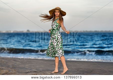 Young beautiful woman wearing hat walking on sand at the ocean beach and looking into the camera. Girl`s hair blowing up on the wind at sunset time.