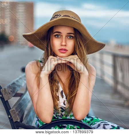 Beautiful blonde young adult woman sitting on the bench wearing hat near ocean beach shore. Girl looking into the camera in city outdoors.