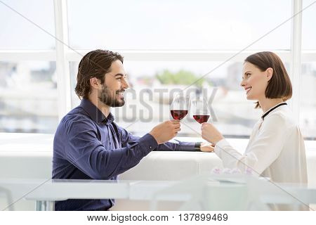 Young loving couple is drinking wine during celebration. They are sitting and clinking glasses. Lovers are looking at each other with love and smiling