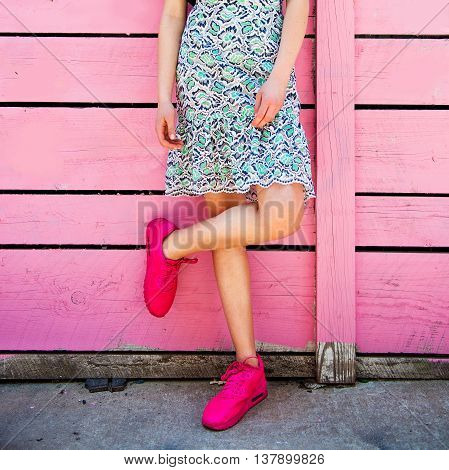Pink sneakers on girl legs on the grunge wooden pink wall background. Street style photo. Girl wearing sneakers and summer skirt.