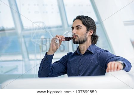 Relaxed young businessman is drinking red wine with pleasure. He is sitting on couch and looking forward with confidence