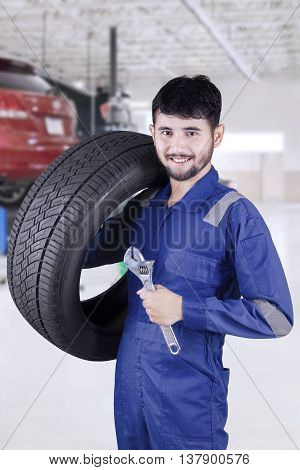 Picture of Arab mechanic holding a tire and spanner while wearing uniform in the workshop